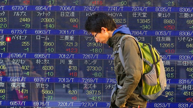 Mann läuft an Tafel mit Börsenkursen vorbei