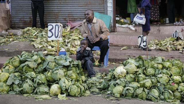 Ein Mann mit einem Kind verkauft Kohl vor einem geschlossenen Markt
