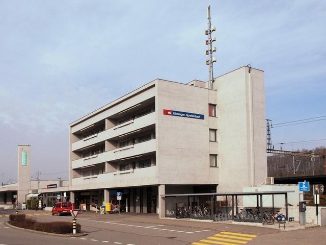 Ein Bahnhofsgebäude, das würfelförmig aus Beton gebaut ist. Es ist das Bahnhofsgebäude von Killwangen-Spreitenbach