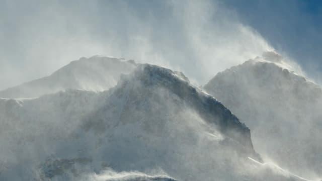Aufgewirbelter Schnee und blauer Himmel.