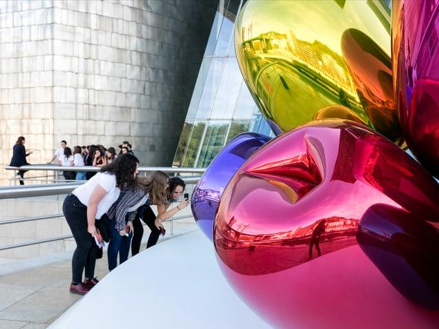 Drei junge Frauen machen ein Foto vor der Blumen-Skulptur von Jeff Koons