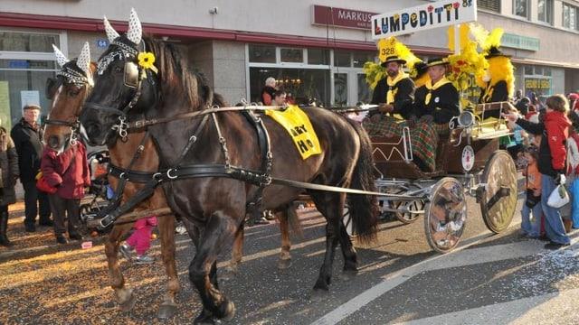 Zwei Pferde ziehen einen Wagen an der Fasnacht in Basel.