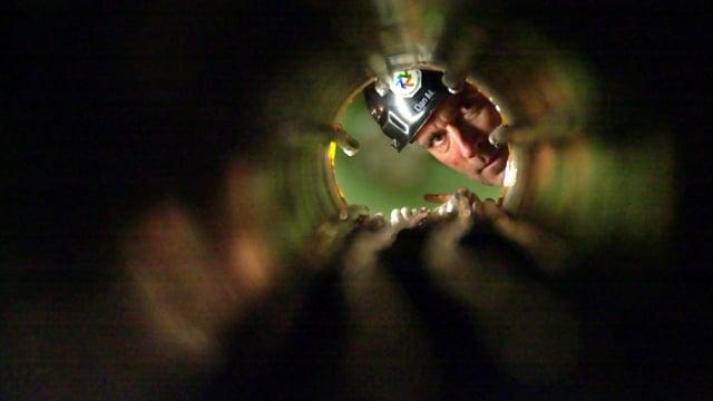 Ein Forscher in einem ehemaligen Bergwerk in Minnesota, das heute der Neutrino-Suche dient, schaut durch ein Rohr.