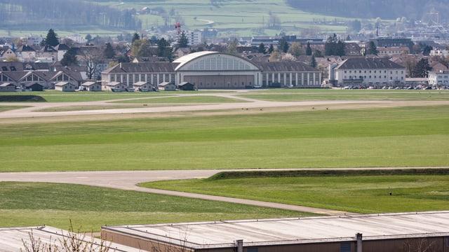 Blick auf den Flugplatz Dübendorf, mit Pisten und Wiesen. Dahinter einn Hangar.