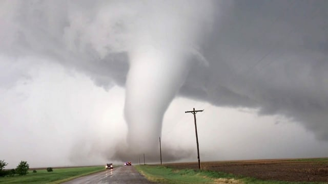 Ein Tornado im Hintergrund, eine Strasse und 2 Autos im Vordergrund.