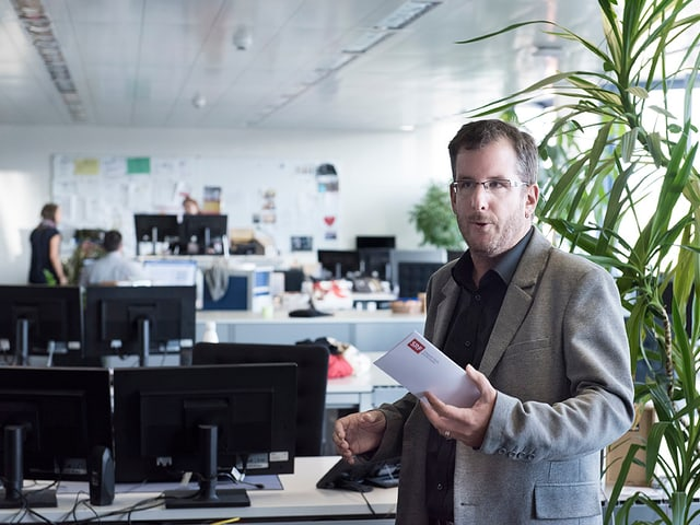 Maurice Velati erklärt vor Arbeitsplätzen im Grossraumbüro