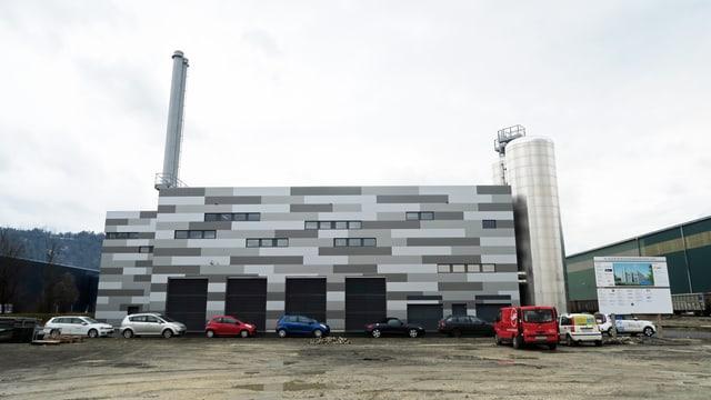 Ein dunkles Industriegebäude mit einem hohen Kamin auf der linken Seite.