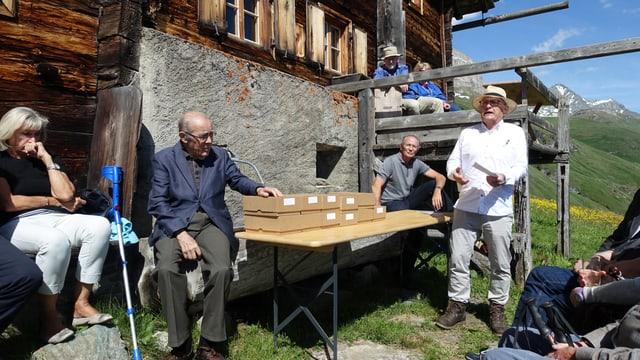 Philipp Egger da l'Uniun cuntrada cultivada Platta preschenta il nov cudesch, preschent vi da la maisa è era Martin Bundi, anteriur president dal Cussegl naziunal.