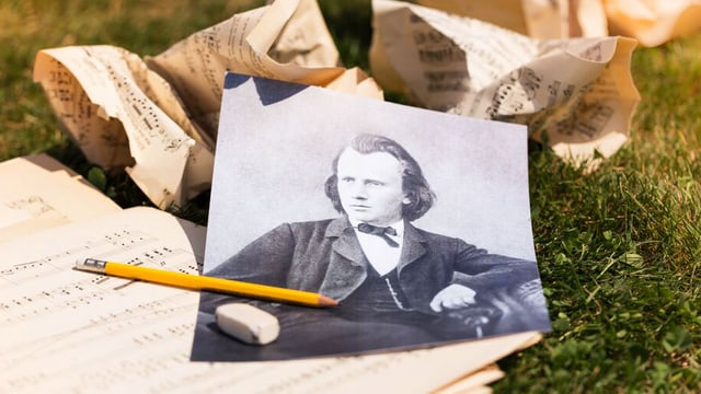 Ein Foto von Brahms auf zusammengeknüllten Noten.