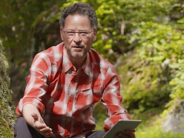 Ein Mann mit Brille im rot-weissen Karohemd draussen in der Hocke und mit einem Tablet in der Hand.