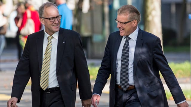 Die beiden Zuger Regierungsräte Peter Hegglin und Heinz Tännler gehen gemeinsam über einen Platz.