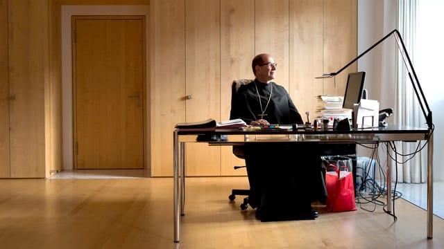 Ein Mann in Mönchskutte an einem modernen Schreibtisch mit Computer sitzend, zum Fenster hinausschauend.