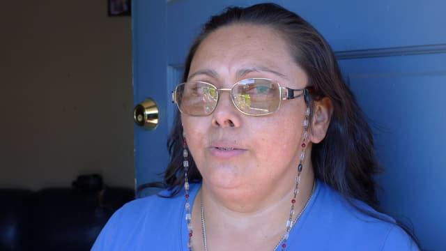 Petra Reynaga vor einer blauen Tür, in einem blauen T-Shirt.