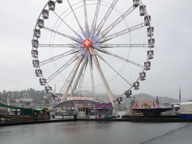 Ein riesen rad steht am Luzerner Messeplatz,  auf der  Seeoberfläche davor erzeugen fallende Regentropfen viele kleine Kreise.