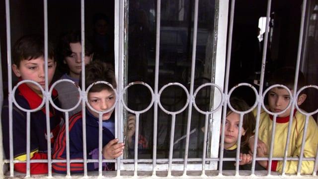 Kinder hinter einer Türe mit Eisenstäben