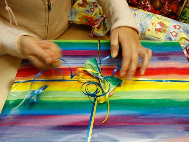 EIn Kind packt ein farbig bepacktes Geschenk aus.