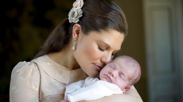Victoria hält die Nase an die Wange ihres Babys.