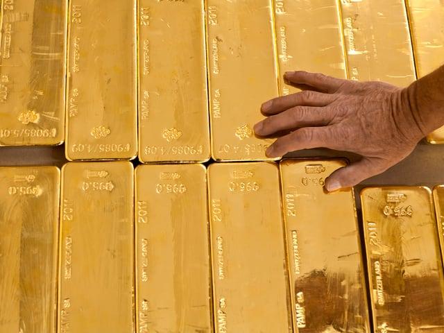 Mann hält seine Hans auf Goldbarren.