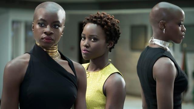 Drei dunkelhäutige Frauen. Die beiden links und rechts haben keine Haare und tragen goldene Ketten, diejenige in der Mitte hat kurze Haare. Sie schauen ernst.