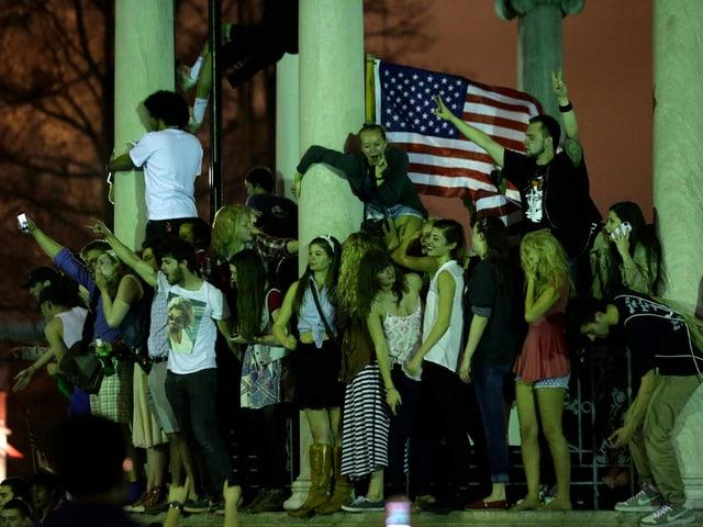 Jubelnde an einem Monument.