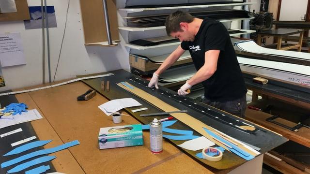 Mann arbeitet und klebt Snowboards zusammen