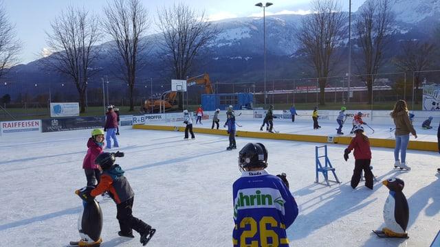 Kinder laufen Schlittschuh auf dem Eisfeld.