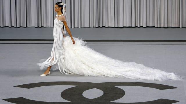 Ein Model auf dem Laufsteg. Am Boden ist das Chanel-Logo.