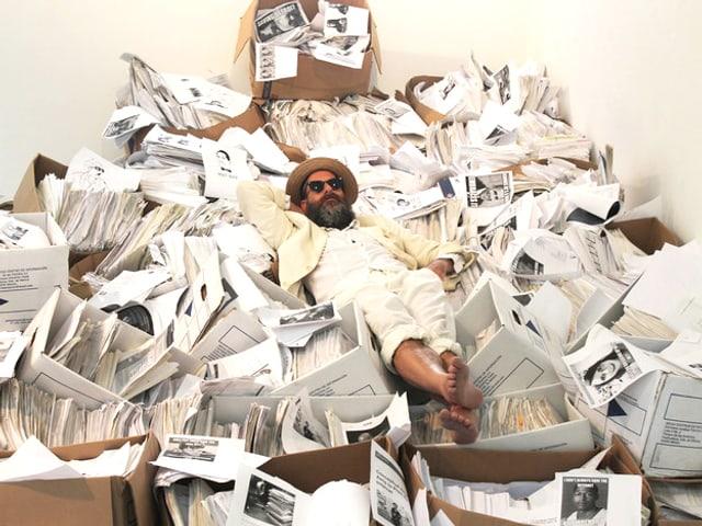 Ein Mann liegt auf einem Berg Papier.