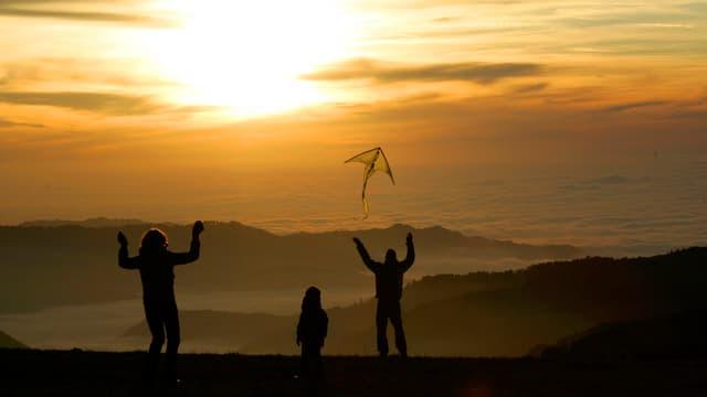 Familie lässt im Sonnenuntergang Drachen steigen
