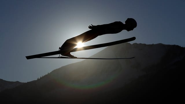 Ein Skispringer befindet sich in der Flugphase.
