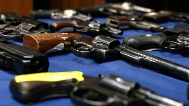 Verschiedene Revolver auf einem Tisch.