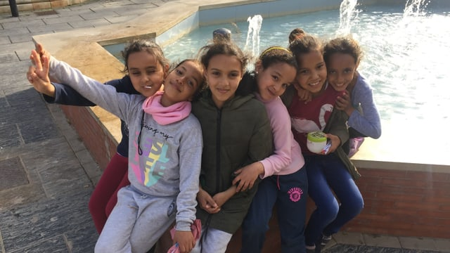 Sechs Mädchen sitzen eng aneinender am Rand eines Springbrunnen.