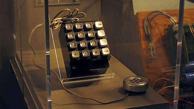 Blick auf einen Schaukasten, in dem eine verkabelte Telefontastatur zu sehen ist.