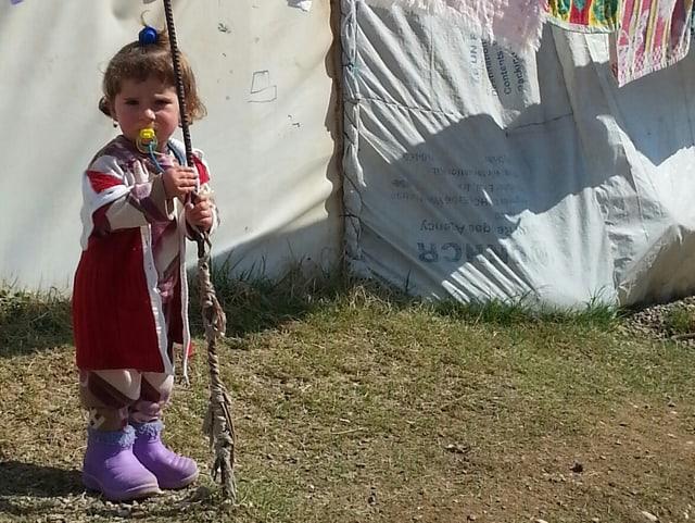 Ein kleines Mädchen mit einem Schnuller im Mund.