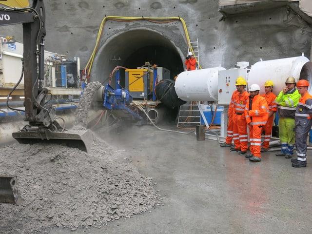 Eine Tunnelbohrmaschine. Daneben stehen ein paar Mineure in orangen Arbeitsanzügen.
