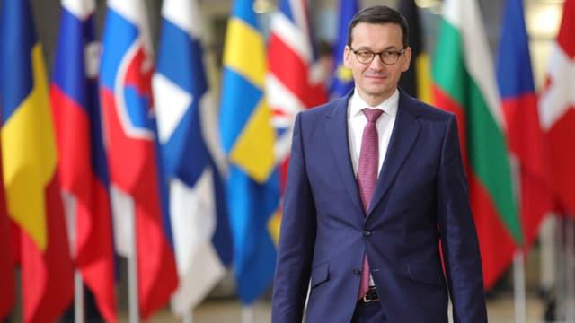 Mateusz Morawiecki vor einer Wand mit Flaggen gehend.