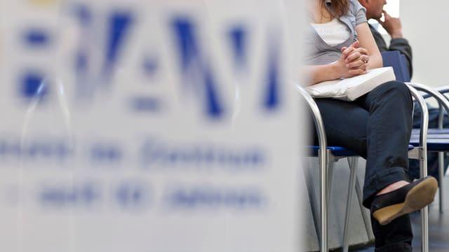 Ein verschwommenes Schild des RAV. Hintergrund sitzt eine Frau.