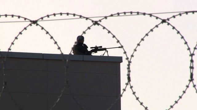 Wächter mit Scharfschützengewehr auf einem Hausdach. Stacheldraht im Vordergrund.