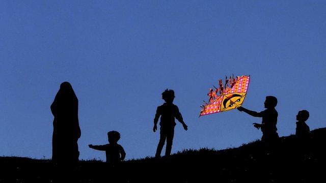 Eine Frau und vier Kinder spielen mit einem Drachen im Wind.