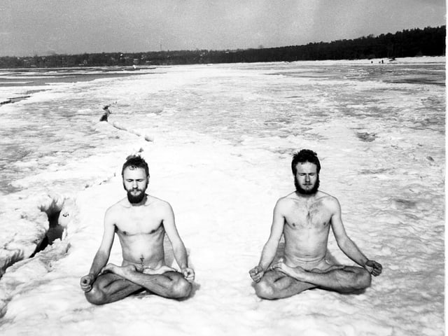 Zwei nackte Männer meditieren im Schneidersitz.