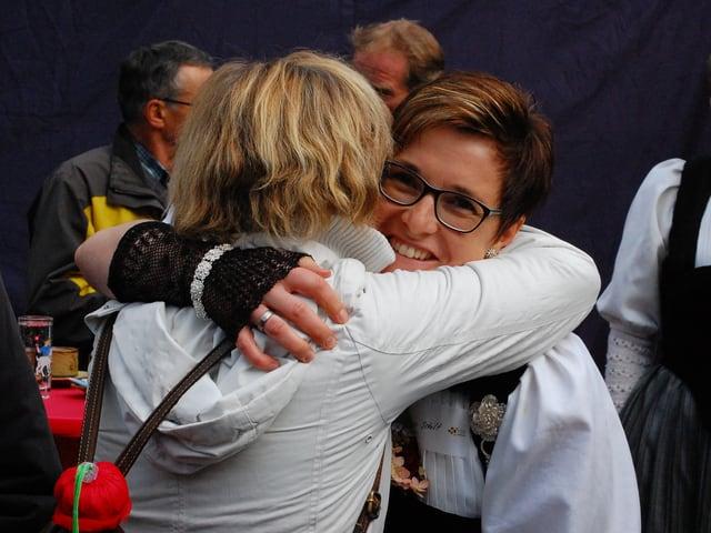 Zwei Frauen umarmen sich erfreut.
