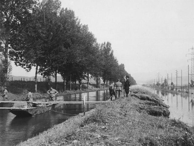 Schwarz-Weiss-Bild: Männer in einem Boot auf dem Fluss.