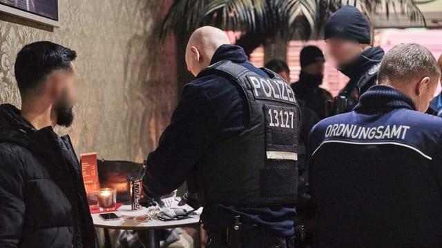 Gasthaus von innen, Polizisten in Uniform. Männer.