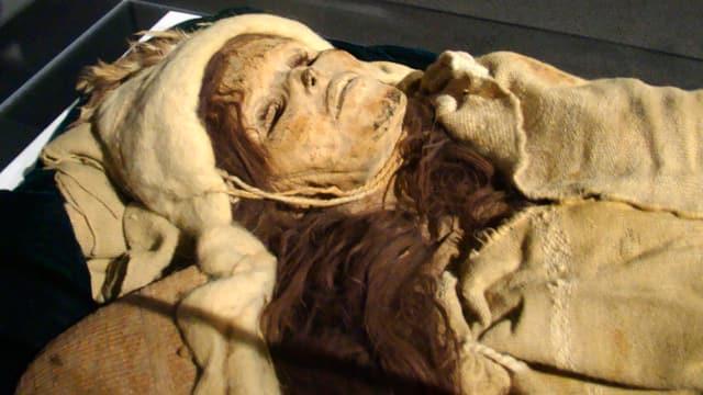Weibliche Mumie mit Mütze und Kleidung