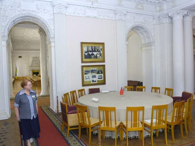 Ein ältere Dame steht neben dem runden Tisch innerhalb des Palasts.