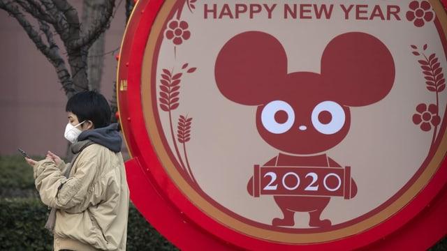 Eine Frau mit Schutzmaske vor einem Neujahrsschild mit der Ratte.