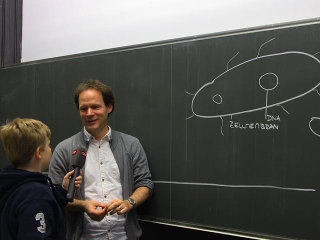 Ein Junge interviewt ein Biologielehrer
