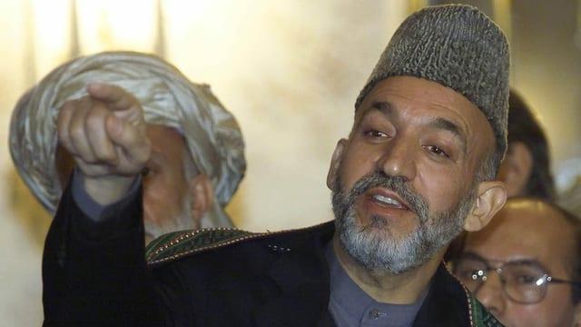 Hamid Karsai zeigt mit dem Finger auf etwas oder jemanden.