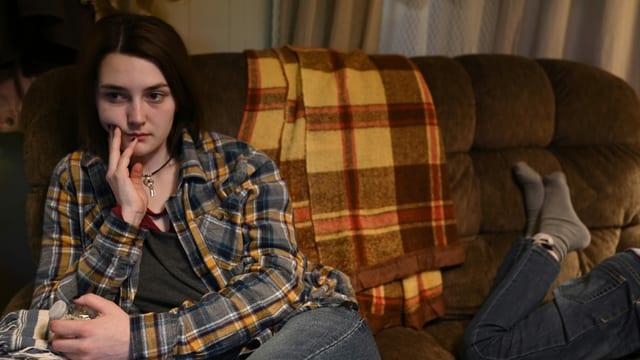 Junge Frau sitzt mit glasigen Augen auf dem Sofa