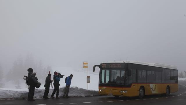 TV-Crew wartet im Nebel auf Postauto, welches soeben vorfährt.